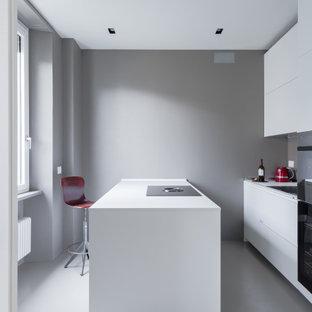 Foto di una cucina parallela moderna con ante lisce, ante bianche, elettrodomestici neri, isola, pavimento grigio e top bianco