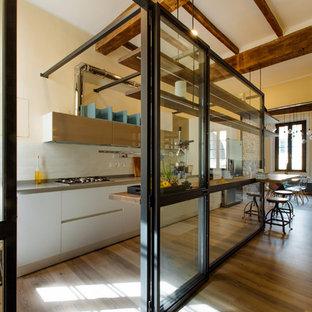 Idee per una cucina minimal di medie dimensioni con ante lisce, ante bianche, paraspruzzi bianco, pavimento in legno massello medio e top grigio