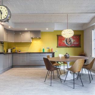 Diseño de cocina comedor en L, ecléctica, grande, sin isla, con armarios con paneles lisos, puertas de armario grises y salpicadero amarillo