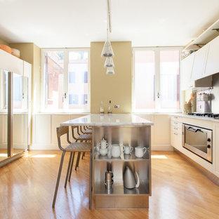 Foto di una cucina design con ante a filo, ante bianche, top in marmo, paraspruzzi a effetto metallico, paraspruzzi con piastrelle di metallo, elettrodomestici in acciaio inossidabile, pavimento in legno massello medio e penisola
