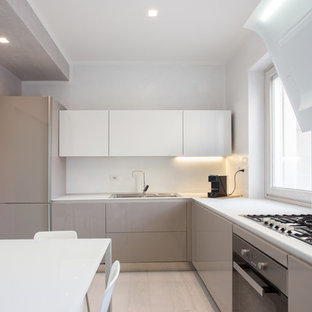 Photo of a mid-sized contemporary l-shaped eat-in kitchen in Other with a drop-in sink, glass-front cabinets, beige cabinets, stainless steel appliances and light hardwood floors.