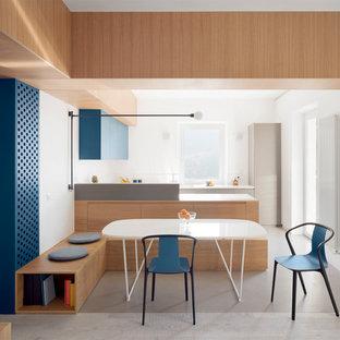 Стильный дизайн: п-образная кухня-гостиная среднего размера в стиле модернизм с одинарной раковиной, фасадами с декоративным кантом, светлыми деревянными фасадами, столешницей из кварцевого композита, белым фартуком, техникой из нержавеющей стали, полуостровом, серым полом и белой столешницей - последний тренд