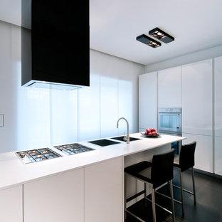 Esempio di un cucina con isola centrale design con lavello a doppia vasca, ante lisce, ante bianche, pavimento nero e top bianco