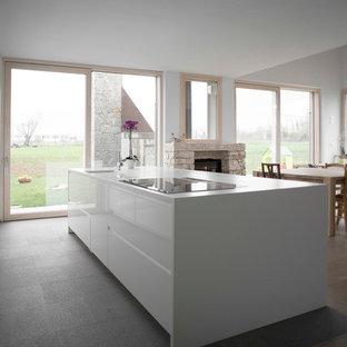 Foto di un'ampia cucina ad ambiente unico contemporanea con ante lisce, ante bianche, pavimento in ardesia e isola