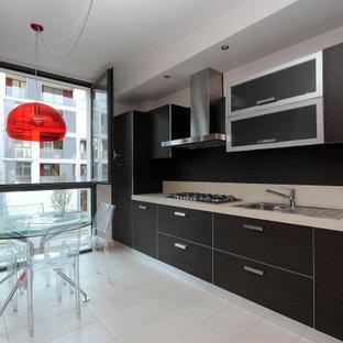 Foto di una cucina lineare minimal di medie dimensioni con lavello da incasso, ante di vetro, ante in legno bruno, elettrodomestici in acciaio inossidabile, pavimento in gres porcellanato, nessuna isola, pavimento beige e top grigio