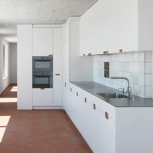 他の地域の中くらいのインダストリアルスタイルのおしゃれなL型キッチン (シングルシンク、フラットパネル扉のキャビネット、白いキャビネット、ステンレスカウンター、白いキッチンパネル、テラコッタタイルのキッチンパネル、シルバーの調理設備、テラコッタタイルの床、赤い床、グレーのキッチンカウンター) の写真