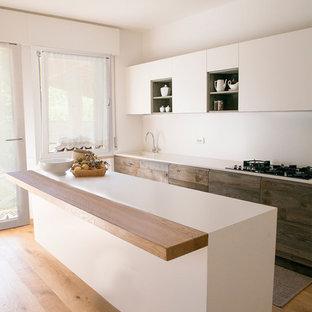 Foto di una cucina abitabile design con parquet chiaro, isola, lavello integrato, ante lisce, ante bianche, top in superficie solida e paraspruzzi bianco