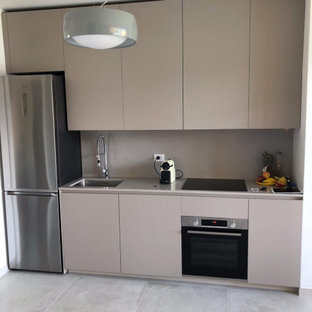 Photo of a small modern single-wall open plan kitchen in Milan with an undermount sink, flat-panel cabinets, beige cabinets, laminate benchtops, beige splashback, black appliances, ceramic floors, no island, grey floor and beige benchtop.