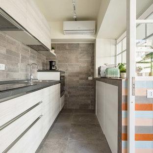 Ispirazione per una cucina a corridoio design con lavello da incasso, ante lisce, ante beige, paraspruzzi grigio, una penisola, pavimento grigio e top grigio