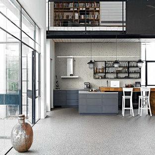 Esempio di una grande cucina industriale con ante grigie, paraspruzzi bianco, paraspruzzi in gres porcellanato, pavimento in gres porcellanato, isola, pavimento grigio, ante lisce e elettrodomestici in acciaio inossidabile