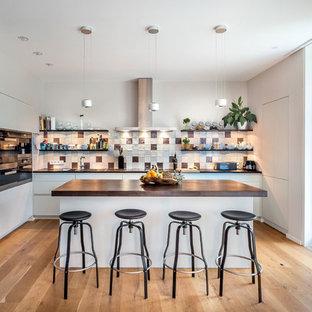 ベルリンの中サイズのカントリー風おしゃれなキッチン (ドロップインシンク、フラットパネル扉のキャビネット、白いキャビネット、木材カウンター、マルチカラーのキッチンパネル、セラミックタイルのキッチンパネル、黒い調理設備、無垢フローリング、茶色い床、茶色いキッチンカウンター) の写真