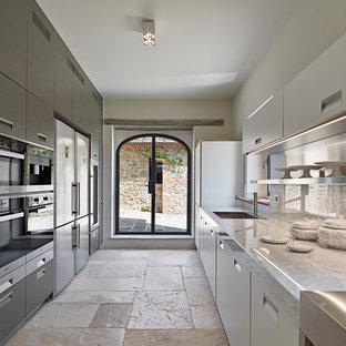 Esempio di una cucina a corridoio contemporanea con lavello sottopiano, ante lisce, ante bianche, paraspruzzi beige, elettrodomestici in acciaio inossidabile e pavimento beige