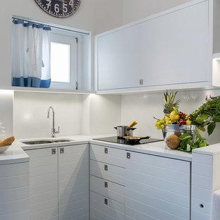 Ispirazione per una piccola cucina a L costiera con lavello a doppia vasca, ante bianche e paraspruzzi bianco