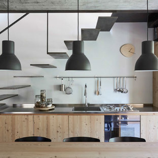 Esempio di una piccola cucina industriale con lavello integrato, ante lisce, ante beige, top in acciaio inossidabile, elettrodomestici da incasso, nessuna isola e top grigio