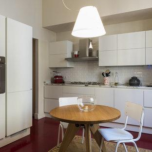ミラノの中くらいのコンテンポラリースタイルのおしゃれなキッチン (ダブルシンク、フラットパネル扉のキャビネット、白いキャビネット、大理石カウンター、白いキッチンパネル、サブウェイタイルのキッチンパネル、シルバーの調理設備、淡色無垢フローリング、アイランドなし、赤い床) の写真