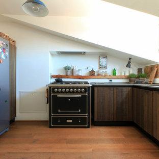 Esempio di una cucina ad U mediterranea chiusa con lavello a vasca singola, ante lisce, ante in legno bruno, paraspruzzi beige, pavimento in legno massello medio, nessuna isola, pavimento marrone e top grigio