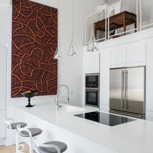 Immagine di una cucina parallela design chiusa e di medie dimensioni con lavello da incasso, ante a filo, ante bianche, top in laminato, parquet chiaro, penisola e top bianco