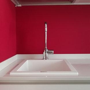 Idéer för att renovera ett avskilt, mellanstort funkis vit vitt parallellkök, med en enkel diskho, släta luckor, vita skåp, rött stänkskydd, klinkergolv i porslin, brunt golv, bänkskiva i kvartsit och rostfria vitvaror