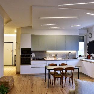 Esempio di una cucina contemporanea con ante lisce, ante bianche, lavello a doppia vasca, paraspruzzi grigio, elettrodomestici neri, pavimento in legno massello medio, nessuna isola e pavimento marrone