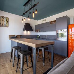 Ispirazione per una cucina industriale con lavello sottopiano, ante lisce, ante grigie, elettrodomestici colorati, parquet scuro, penisola, pavimento marrone e top grigio