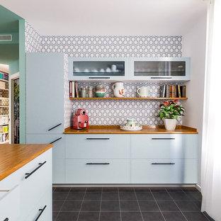 ミラノの中サイズのビーチスタイルのおしゃれなキッチン (フラットパネル扉のキャビネット、木材カウンター、セラミックタイルの床、黒い床、青いキャビネット、マルチカラーのキッチンパネル) の写真