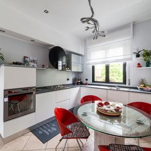 Immagine di una piccola cucina design con lavello integrato, ante lisce, ante in legno chiaro, top in quarzo composito, paraspruzzi grigio, elettrodomestici in acciaio inossidabile e pavimento con piastrelle in ceramica