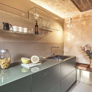 Esempio di una cucina industriale con lavello a vasca singola, ante lisce, ante grigie, pavimento in cemento, pavimento grigio, top in vetro, paraspruzzi grigio e top grigio