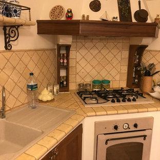 他の地域の中サイズのカントリー風おしゃれなキッチン (ダブルシンク、レイズドパネル扉のキャビネット、中間色木目調キャビネット、大理石カウンター、ベージュキッチンパネル、大理石の床、パネルと同色の調理設備、磁器タイルの床、ピンクの床、ベージュのキッチンカウンター) の写真