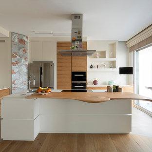 Modern inredning av ett avskilt, mellanstort vit vitt l-kök, med en undermonterad diskho, släta luckor, svarta vitvaror, betonggolv, en köksö, grått golv och skåp i mellenmörkt trä