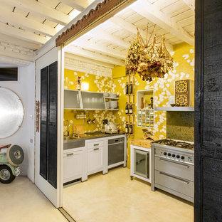 Esempio di una piccola cucina ad U eclettica chiusa con lavello da incasso, ante con bugna sagomata, ante bianche, top in acciaio inossidabile, elettrodomestici in acciaio inossidabile e pavimento in gres porcellanato