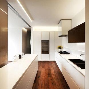 ヴェネツィアの大きいコンテンポラリースタイルのおしゃれなキッチン (一体型シンク、フラットパネル扉のキャビネット、白いキャビネット、人工大理石カウンター、白いキッチンパネル、シルバーの調理設備、濃色無垢フローリング) の写真