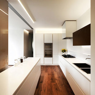 Design ideas for a large contemporary l-shaped open plan kitchen in Venice with an integrated sink, flat-panel cabinets, white cabinets, solid surface benchtops, white splashback, stainless steel appliances, a peninsula and dark hardwood floors.