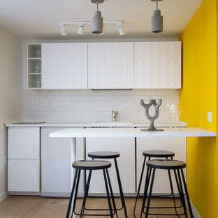 Ispirazione per una cucina lineare design di medie dimensioni con ante bianche, top bianco, ante lisce, paraspruzzi bianco, penisola, pavimento marrone e pavimento in legno massello medio