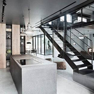 Idee per una cucina minimal di medie dimensioni con ante lisce, ante in legno chiaro, top in cemento, pavimento in cemento e isola