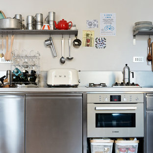 This is an example of a mid-sized industrial single-wall eat-in kitchen in Milan with an integrated sink, open cabinets, stainless steel cabinets, stainless steel benchtops, grey splashback, concrete floors, no island and grey floor.