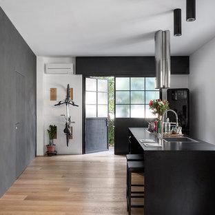 Immagine di una cucina industriale di medie dimensioni con lavello a vasca singola, elettrodomestici neri, parquet chiaro, isola, pavimento beige e top nero