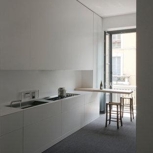 Foto di una cucina lineare moderna chiusa e di medie dimensioni con lavello a vasca singola, ante lisce, ante bianche, top in quarzo composito, paraspruzzi bianco, elettrodomestici da incasso, moquette, penisola e pavimento grigio
