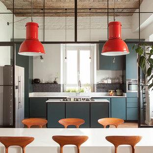 Immagine di una cucina industriale con ante lisce, ante blu, pavimento in legno massello medio, pavimento marrone e top bianco