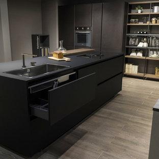 ナポリの中くらいのモダンスタイルのおしゃれなキッチン (ドロップインシンク、フラットパネル扉のキャビネット、黒いキャビネット、グレーのキッチンパネル、シルバーの調理設備、竹フローリング) の写真
