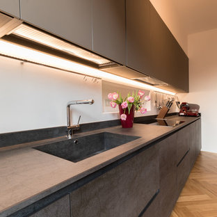 Photo of a mid-sized contemporary galley separate kitchen in Milan with beaded inset cabinets, grey cabinets, an integrated sink, tile benchtops, light hardwood floors and brown floor.