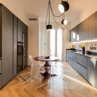 Esempio di una cucina parallela minimal chiusa e di medie dimensioni con ante grigie, nessuna isola, ante lisce, elettrodomestici in acciaio inossidabile, pavimento in legno massello medio, pavimento marrone, lavello integrato e top in cemento