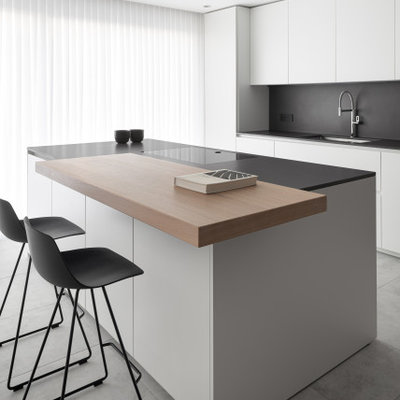 Kitchen - mid-sized contemporary galley gray floor kitchen idea in Venice with an undermount sink, flat-panel cabinets, white cabinets, black backsplash, an island and black countertops