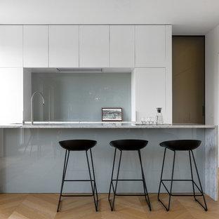 Esempio di una grande cucina moderna con lavello sottopiano, ante lisce, ante bianche, top in marmo, paraspruzzi grigio, paraspruzzi con lastra di vetro, pavimento in legno massello medio, isola, pavimento beige, top bianco e elettrodomestici da incasso
