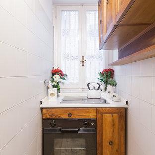 Immagine di una piccola cucina country con ante con riquadro incassato, ante in legno scuro, top in superficie solida, elettrodomestici neri e pavimento in mattoni