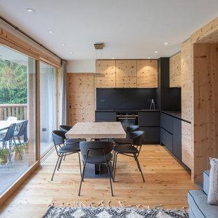 Esempio di una cucina stile rurale con ante lisce, ante nere, paraspruzzi nero, elettrodomestici neri, parquet chiaro e top nero