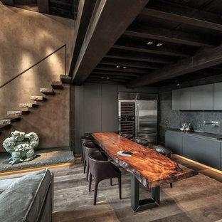 Immagine di una cucina minimal con lavello sottopiano, ante lisce, ante grigie, elettrodomestici in acciaio inossidabile, parquet scuro, nessuna isola, pavimento marrone e top grigio