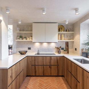 Inspiration för ett medelhavsstil vit vitt u-kök, med en enkel diskho, släta luckor, skåp i mellenmörkt trä, grått stänkskydd, en halv köksö och orange golv
