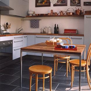 Esempio di una cucina country di medie dimensioni con ante lisce, ante bianche, top in legno, paraspruzzi bianco, elettrodomestici in acciaio inossidabile, nessuna isola e pavimento nero