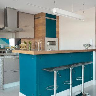 Foto di una cucina parallela design con ante lisce, ante beige, top in granito, paraspruzzi a specchio, elettrodomestici in acciaio inossidabile, isola e pavimento grigio
