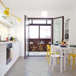 Esempio di una cucina design con ante lisce, ante bianche, paraspruzzi giallo, elettrodomestici in acciaio inossidabile, nessuna isola, pavimento grigio e top bianco